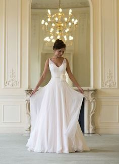 Elegant sleeveless wedding dress features strapless sweetheart underskirt in v-neckline overlay. Lace bodice topped by a-line blush color chiffon skirt. Matching with sash.
