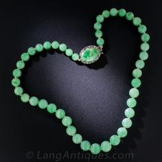 A fresh and pretty early 20th century necklace composed of 45 light-to-medium apple green natural Jade beads - ranging from 6.88 millimeters to 9.67 millimeters. The necklace measures 16 inches long and closes with a silver clasp set with a matching carved jade oval.