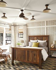 The birch-patterned wall covering gives this guest room a rustic feel year-round. Draperies mimic the effect without feeling matchy-matchy and the reclaimed wood bed, hand-knotted rug, and barn lights from Schoolhouse Electric reinforce the tree house vibe.