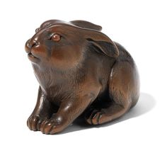 A wood netsuke of a hare By Issan, 19th century Seated, facing ahead and its head slightly raised with an alert expression, its ears drawn back and its forelegs outstretched, the well-toned wood is slightly worn and the eyes are inlaid with amber, signed in an oval reserve Issan