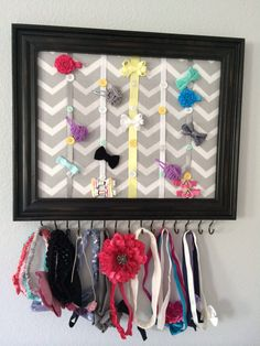 Hairband hair clip organizer. My sister made this adorable organizer for me. She took a picture frame, took out the glass. Covered the cardboard that came in the frame with fabric. Added ribbons, sewed on buttons to hold the ribbons, and screwed in eye hooks to the bottom. Now I have a place to hang all of my daughters headbands and a place to have all her clips organized. Children's organization. Bathroom hair accessory accessories storage headband hair clip DIY idea bow ribbon holder…