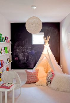 Fun Tee Pee in the corner of this cute child's room and great calkboard wall to write and draw on. Also love the book shelving.