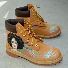 These one-of-a-kind hand-painted Timberland Classic Wheat Boots feature a beautiful girl on the outside of each shoe. The words Black Lives Matters is written over and over again in the background. Th