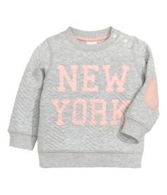 Sweatshirt in quilted fabric with a printed text design at front. Snap fasteners on one shoulder, long sleeves with contrasting elbow patches, and ribbing at cuffs and hem.