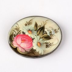 Floral Mother of Pearl Pin - #Russian #Jewelry - Jewelry - $52.99 This luminescent pin is truly a work of art, as it features a miniature painting of a floral arrangement (roses and daisies) which is exquisitely detailed. The brooch is made of mother-of-pearl base that is nested into a German silver frame with a simple pin on the back. Each brooch is painted in the classical Fedoskino style. #Fedoskino is the famous Russian school of miniature #painting