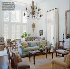 dramatic pale living room | high ceilings | pale blue sofa | French chandelier | white walls