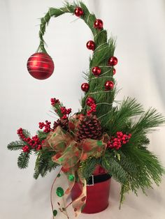 Create a Grinch Christmas Tree using fresh holiday foliage, artificial berries, balls and pinecones—all decorated in a Santa tin.