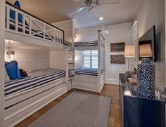 bunk room at the beach cottage.  classic coastal white and navy color scheme and crisp white shiplap walls.