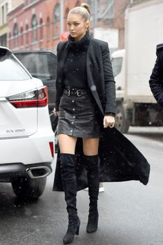 The model braves a snow flurry on her way to a Sports Illustrated event wearing a turtleneck and black leather mini by The Kooples with OTK suede boots.