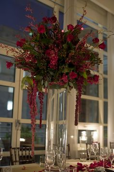 A tall centerpiece featuring red mokara orchids, burgundy james story orchids, red roses and red amaranthus.  To view our entire selection please visit us at www.starflor.com #flowers #events #eventdecor Red Wedding Decorations, Winter Wedding Centerpieces, Wedding Arrangements, Flower Centerpieces, Tall Centerpiece, Burgundy Floral Centerpieces, Party Centerpieces, Floral Arrangements, Table Decorations
