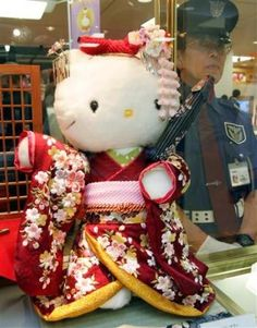 Japanese kimono clad Hello Kitty doll priced at 1.05 million yen ($8,991) is displayed next to a security guard at Tokyo's Mitsukoshi department store in Tokyo July 25, 2006. REUTERS/Yuriko Nakao