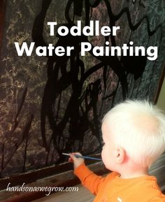 Painting with water on the chalkboard. A perfect activity for a toddler!