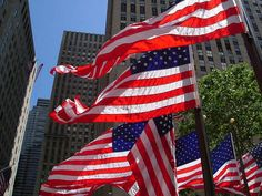Multiple flags flap in the wind at Rockefeller Plaza in New York.