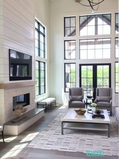 This is a dream house! Cream walls, grey chairs, limestone fireplace and big black Windows. Perfection.