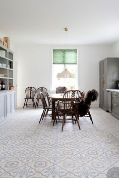 patterned tile floor, grey cabinets, brass hardware, on opposite wall white subway tile with grey grout