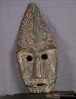 Masque avec une belle patine noire, des dessins géométriques sculptés sur les joues et le sommet du crâne. La tête est pointue et possède en son sommet une petite tête sculptée. Ce masque n'était pas destiné à être porté, mais à être accroché à un mur.