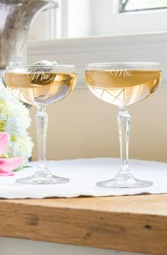 Vintage glamour and a festive spirit come alive with these '30s-inspired, champagne glasses etched in honor of you and your new spouse.