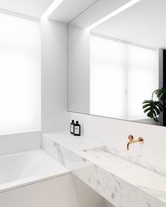 Marble vanity runs over bathtub creates unusual lines in this elegant bathroom
