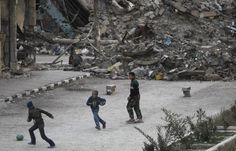 footynions:  Children play football in a damaged street in Deir al-Zor, eastern Syria.
