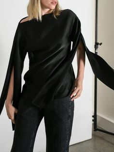 Christopher Esber's Ilona blouse is an effortless off the shoulder black satin top with long split sleeves. The sleeves can be worn loose or tied to create a knot detail.Details100% ViscoseWorn with Rachel Comey Trigger JeansSize and FitFits true to sizeSizes shown are AUModel wears size 8 (AU)Model is 175cm / 5'9inAs seen on HarperandHarley