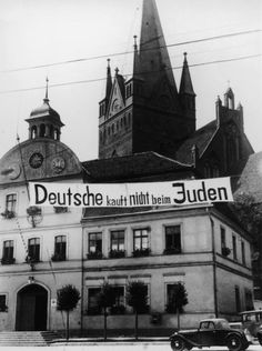 circa 1937: A banner reading 'Deutsche, kauft nicht beim Juden' ('Germans, do not buy from Jews') in front of the Fasanenstrasse Synagogue in Berlin, Germany. The synagogue was later burned by Nazis during the 'Kristallnacht' riots on November 9, 1938. (Photo by Anthony Potter Collection/Getty Images)