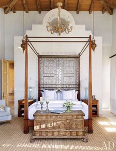 At an oceanside villa in Mexico, the master bedroom's Réplicas y Originales Ornelas bed is set against tin doors that open onto the adjacent bath; the trunk is a Spanish antique, and the abaca rug is by Beauvais Carpets.