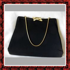 "🌺HOST PICK🌺Vintage H.L. Black Fabric Clutch This is a  gorgeous vintage 50's/60's, H.L. brand, black fabric clutch evening purse, with an optional gold tone chain handle. It features one large compartment. The lining is beige fabric. It has a fabric covered frame with a snap closure accented with a pretty bow accented with crystals. It measures 8"" long, 5"" tall, and 1.5"" deep.  The handle drop is 5"".  In very good vintage condition.  Showing minimal wear. What a fabulous classy purse! H.L…"
