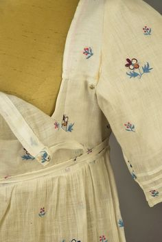 "WHITE COTTON MUSLIN DRESS with EMBROIDERED SPRIGS, c. 1800 - whitakerauction  Tambour-embroidered with polychrome pansies and tiny sprigs, fall-open bodice having short sleeve with four narrow tucks, a wider tuck down the center front crosses another tuck above the ruffled hem, center back having ties around to front, shoulder backing stamped with large ""RD"" and numbers visible through muslin."