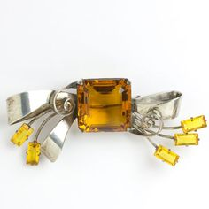 A gorgeous faceted, square-cut deep citrine glass stone forms the center of this 1940s Retro Modern sterling silver bow brooch.