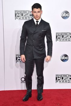 Nick Jonas looking dapper in a black suit at the 2014 AMAs red carpet.