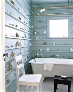 This entire bathroom becomes an homage to the sea with floor to ceiling shelves for nautical treasures.