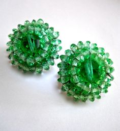 Green cluster crystal earrings by VOGUE with faceted beads...signed vintage:  Enticing clip earrings by VOGUE in shades of light and medium spring green faceted crystals. There are 2 circular layers of the crystals with a large faceted crystal on top. Earrings are nicely constructed with no lose beads. This is a fresh and sophisticated green tone that adds interest to your face. Wear it with a crisp white shirt....refreshing look.  Size .... 1 diameter Height .... 1/2 Hallmark .... signed…