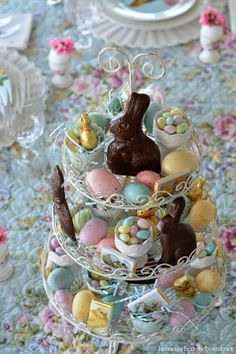 An Easter table centerpiece with chocolate bunnies, candy eggs, egg cups and Easter eggs   homeiswheretheboatis.net #spring #tablescape