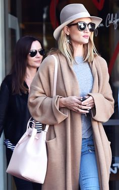 Rosie Huntington-Whiteley wears a fedora, gray tee, oversized coat, blush bucket bag, and Elisabeth Bell's Sea Urchin Star earrings.