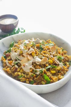 Warm curried quinoa salad with carrot, corn, sultanas, coriander and almonds, topped off with a creamy yoghurt tahini dressing!