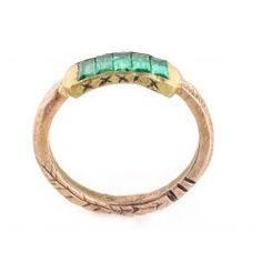 Five emeralds in the glowing colors of the northern lights sit within a channel of 14k rose gold. Band is hand-hewn and etched with small organic markings. 2mm thickness. Emerald channel is 4.5mm.