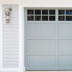 Cladding painted colourbond shale grey, Door painted Colourbond Windspray, Sconce from Emac & Lawson Custom built, hand painted traditional timber garage door with V-Joint lining board and batten detail at our Avalon Beach new home construction by Garage Doors, Hamptons House, Beach House Exterior, Timber Garage Door, Garage Door House, Garage Door Colors, Garage Door Paint, Garage Door Types, Timber Garage