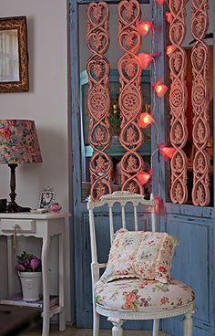 Pequenas lâmpadas envoltas por tecido e tule dão o algo a mais ao biombo com partes de madeira entalhada