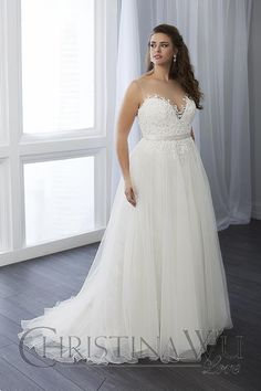 A sheer Sabrina neckline tops the lace-appliqued sweetheart bodice of this Christina Wu Love 29296 plus size wedding dress, with a satin belt and corset back. Flaunting an A-line silhouette, it finishes in a gathered tulle skirt that cascades to a chapel train.