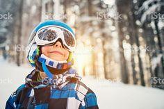 Little boy skiing in snowy forest on sunny winter day Стоковые фото Стоковая фотография