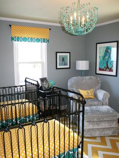 Yellow, teal, black and gray are combined in this contemporary twins nursery with black metal cribs, a teal metal chandelier and a gray armchair and ottoman.