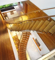 Sky Garden House by Guz Architects, Singapore ~ A staircase with a glass balustrade and wooden steps snakes across the stairwell.