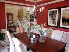 This dining room features artwork on the walls, covering the bold red paint. Do you like the richly stained wood table?