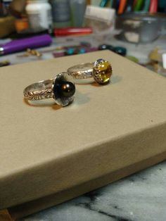 2rings stones set...9 1/2 size yellow synthetic diamond Cab set in sterling silver...7 1/4 size sterling flower multi-colored genuine Tahitian Pearl..these are for sale on my facebook page..
