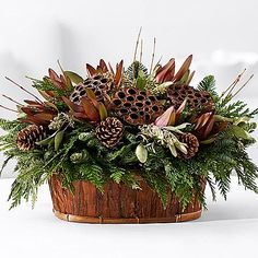 Rustic Natural Holiday Basket - Fresh holiday greens provide a verdant backdrop to burgandy protea, lotus pods and festive pinecones. Winter Floral Arrangements, Christmas Flower Arrangements, Christmas Flowers, Noel Christmas, Rustic Christmas, Christmas Wreaths, Christmas Crafts, Country Christmas Decorations, Xmas Decorations