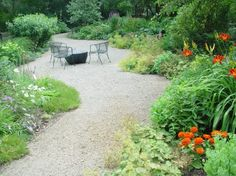 This decomposed gravel path is large enough to accomodate seating in the garden.  The gravel is contained by aluminum edger strip to keep it from migrating into the garden.  However the perennials are planted close enough to that edge to encourage them to spill over.  This giving the garden a relaxed and low key feeling without loosing its strong sense of shape.