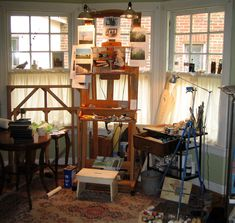 Love the light in this studio.  I like the 2 big lights clamped to the top of the easel.  Also like that it's kind of messy with paint tubes and stuff, like my studio.  I would never paint on that rug though - linoleum floors for me!