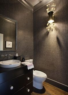With its carbon-gray grass cloth wall covering (part of the Glam Grass collection from Phillip Jeffries), this powder room has a sleek, sexy feel. Adding to the appeal: a sparkly light fixture from Boyd Lighting, a dark wood vanity with a shallow white vessel sink and a silver-framed mirror.