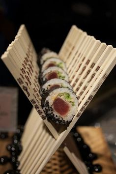 ahi tuna sushi rolls with black sesame and pink pickled ginger festively displayed in a row of crossed chopsticks.