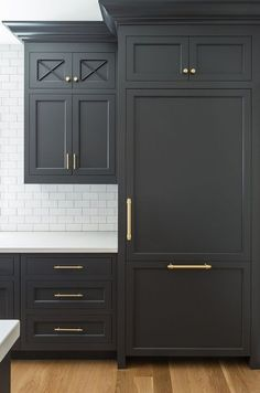 Paint color is Benjamin Moore 1617 Cheating Heart. Benjamin Moore 1617 Cheating Heart is a dark grey, almost black paint color and it looks gorgeous when combined with brass hardware and a white countertop. #kitchen #cabinet #ideas